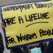 Worker with placard demanding unemployment benefits